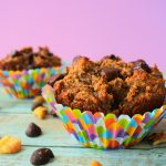 A close up image of a banana nut dark chocolate muffin in a colorful paper liner surrounded by dark chocolate chips and walnuts