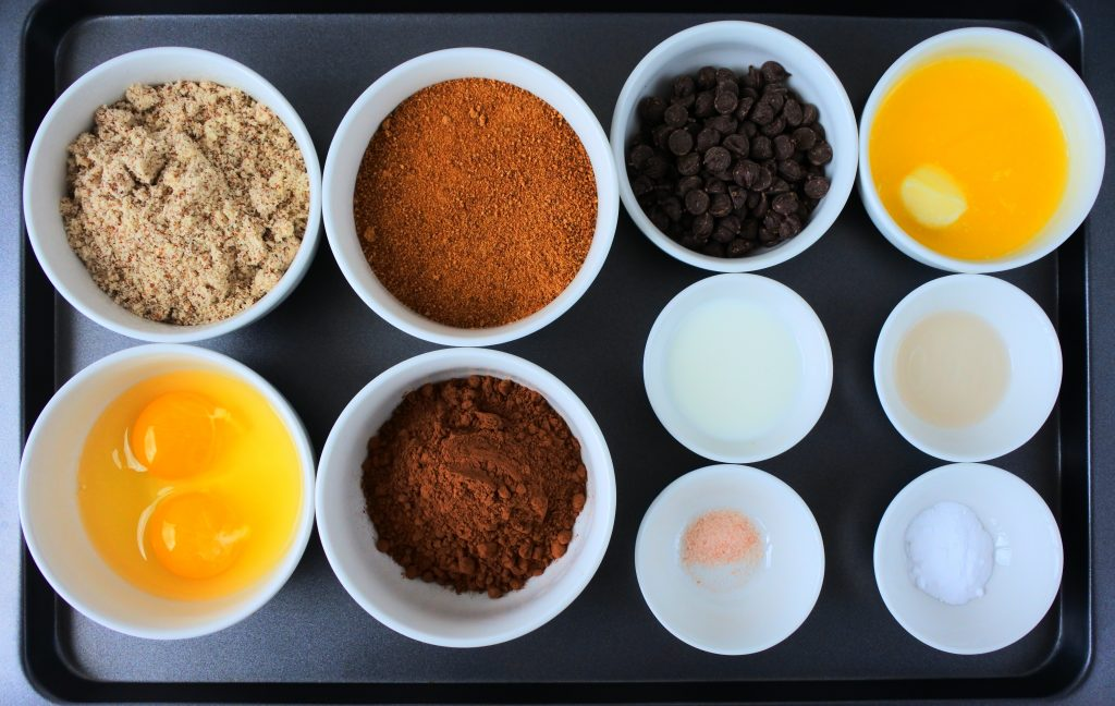 An overhead image of a tray of bowl containing the following ingredients: almond flour, eggs, coconut sugar, cocoa powder, dark chocolate chips, melted butter, a splash of milk, vanilla extract, salt and baking powder.