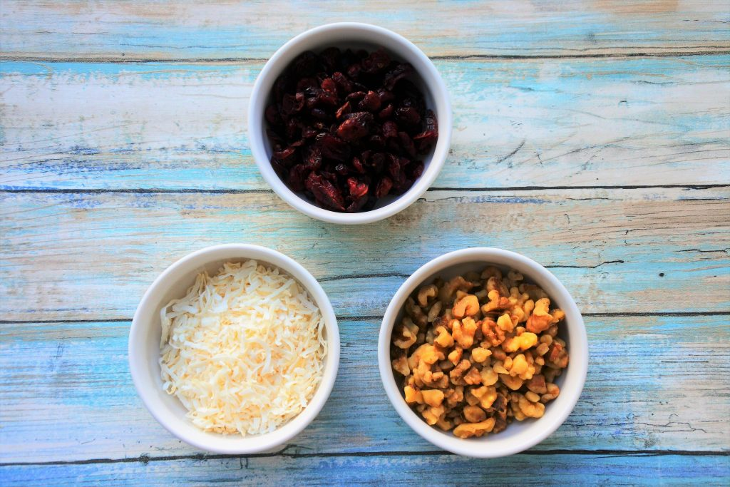 An overhead image of three bowls containing dried cranberries, shredded coconut and walnut pieces