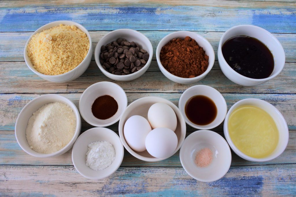 An overhead image of bowls of ingredients for Gluten Free Double Chocolate Chip Muffins including almond flour, coconut flour, chocolate chips, cocoa powder, maple syrup, extra light olive oil, vanilla extract, salt, eggs, espresso powder and baking powder