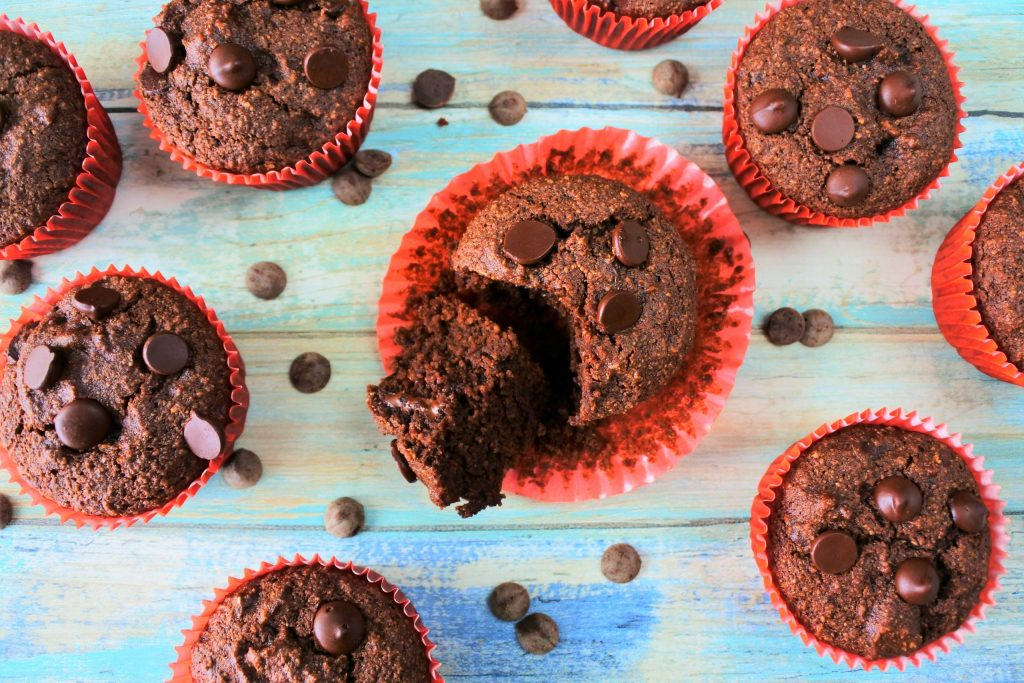 An overhead image of a gluten free double chocolate muffin with the paper liner peeled off and the muffin cut open