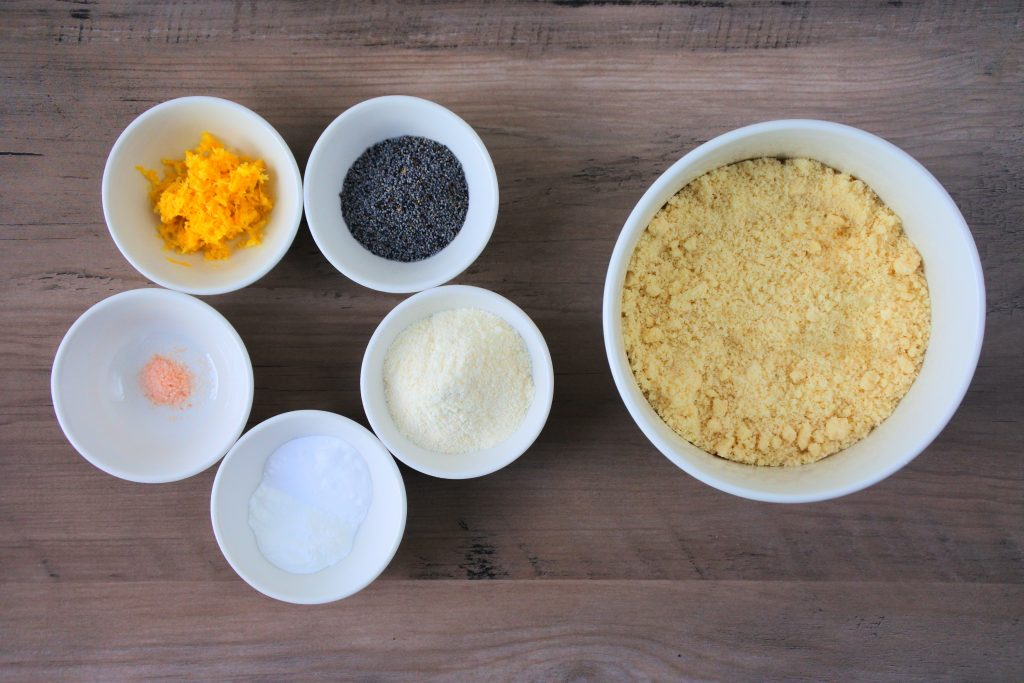 An overhead image of bowls of ingredients including blanched almond flour, coconut flour, baking powder and baking soda, salt, poppy seeds, and lemon zest