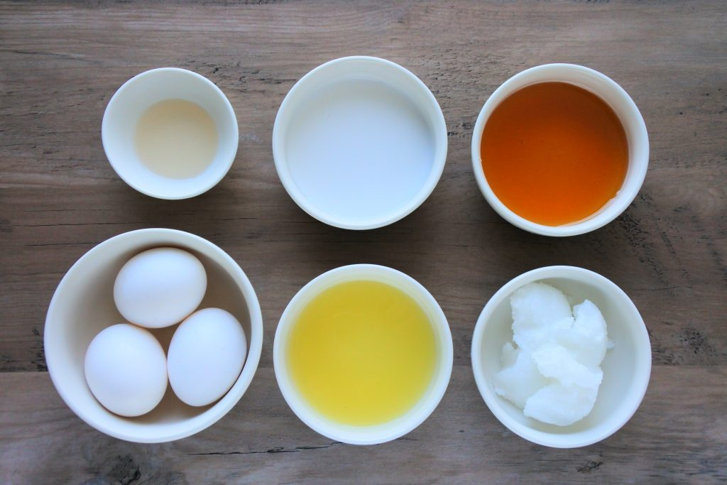 An overhead image of bowls containing eggs, lemon juice, coconut oil, honey, coconut milk, and vanilla extract.