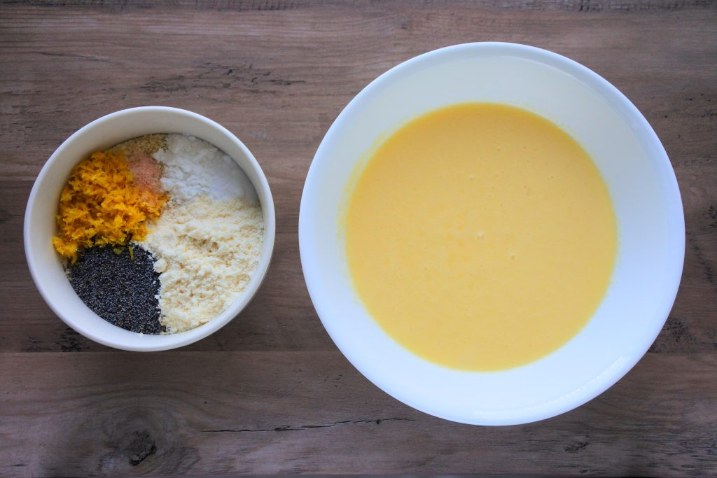 An overhead image of two bowls, one containing dry ingredients and the other containing blended wet ingredients