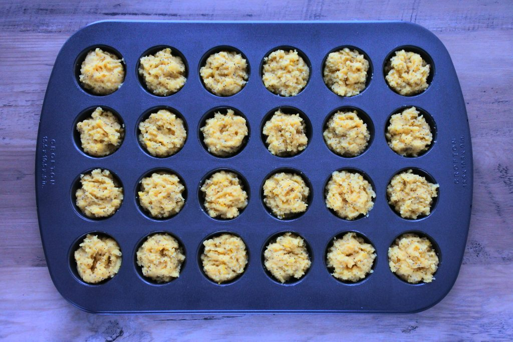 An overhead image of a mini muffin tray filled with lemon poppyseed muffin batter