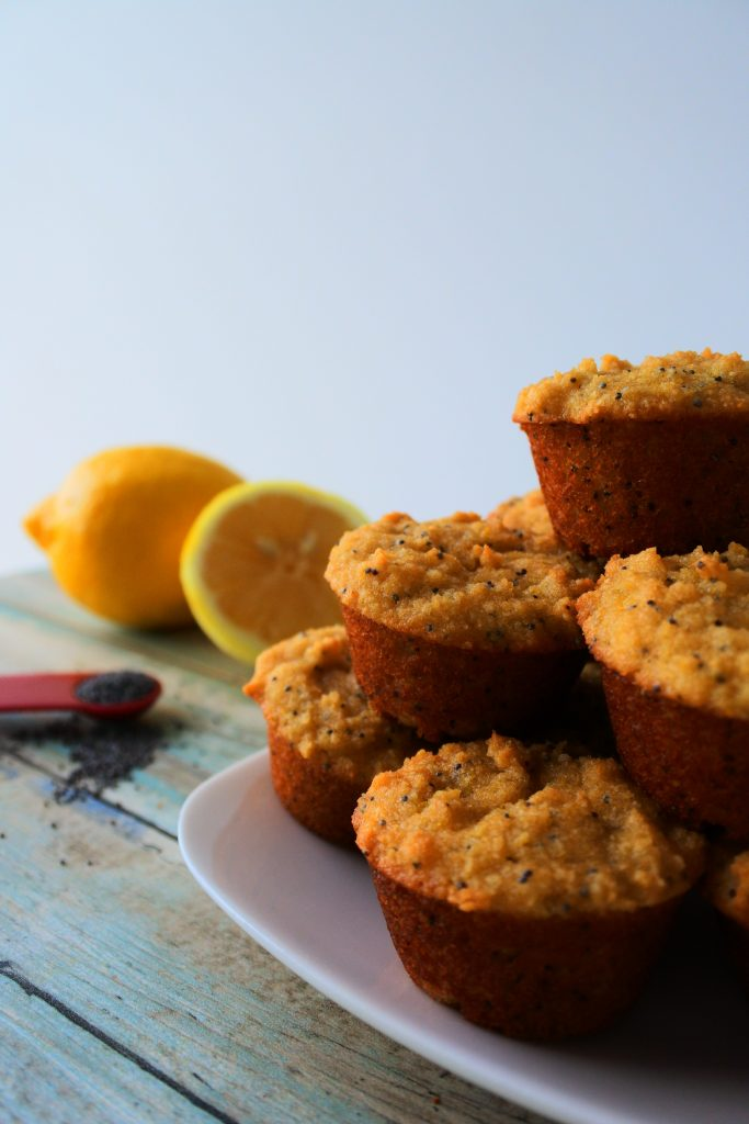 A head on image of a stack of mini lemon poppyseed muffins on a plate with a lemon and teaspoon measure of poppyseeds in the background