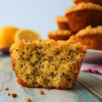 A head-on image of a close up of a split lemon poppyseed muffin with a plate of muffins and fresh lemons in the background