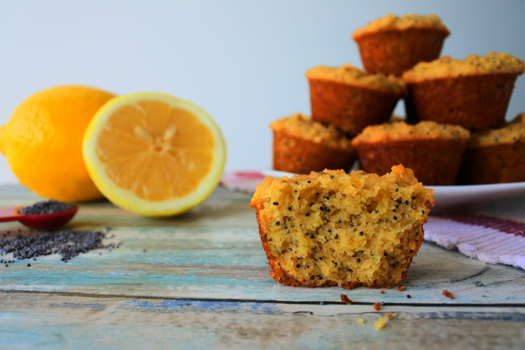 A head-on image of a close up of a split lemon poppyseed muffin with a plate of muffins, fresh lemons, and a teaspoon measure of poppyseeds in the background
