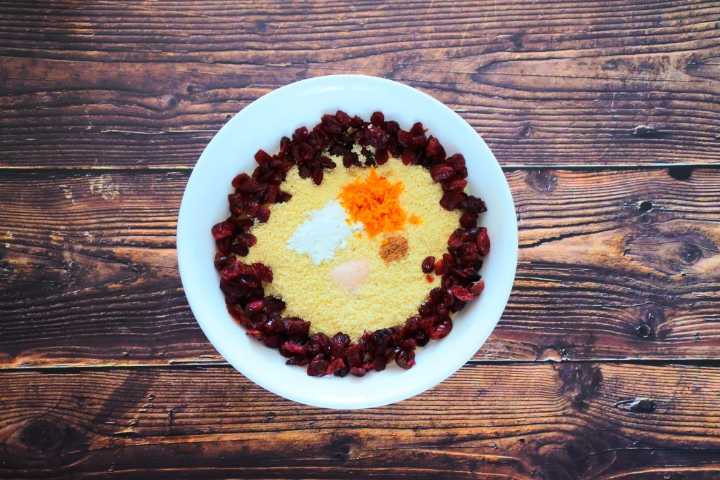 An overhead image of a bowl of almond flour surrounded by dried cranberries as well as salt, nutmeg, orange zest and baking powder.