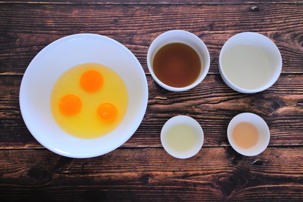An over head image of bowls containing ingredients including cracked eggs, maple syrup, coconut oil (melted), orange extract and vanilla extract.