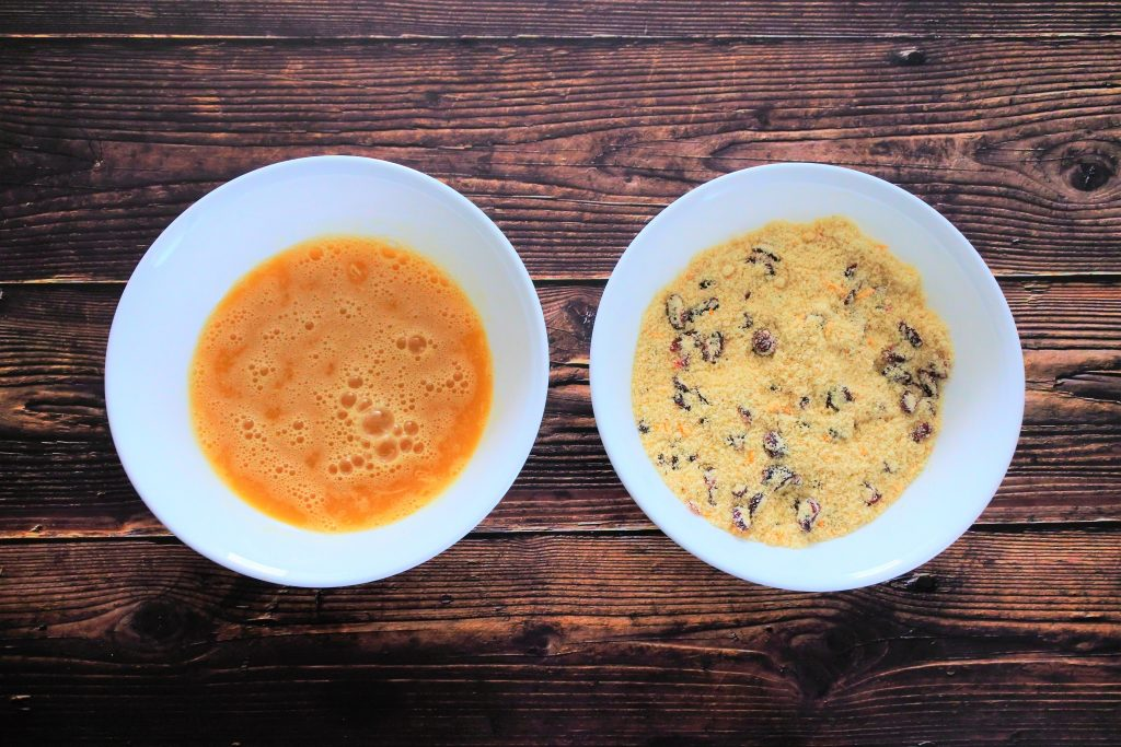 An overhead image of two bowls of mixed wet and mixed dry ingredients for an orange cranberry muffin batter
