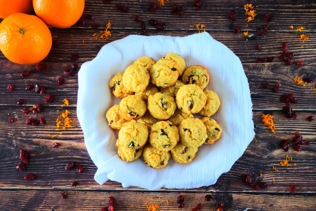 An overhead image of a pile of orange cranberry mini muffins on a white cloth surrounded by dried cranberries and orange zest with three whole oranges in the top left corner