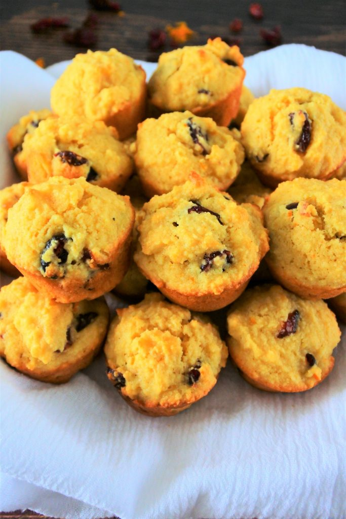 A close up image of a pile of orange cranberry mini muffins on a white cloth.