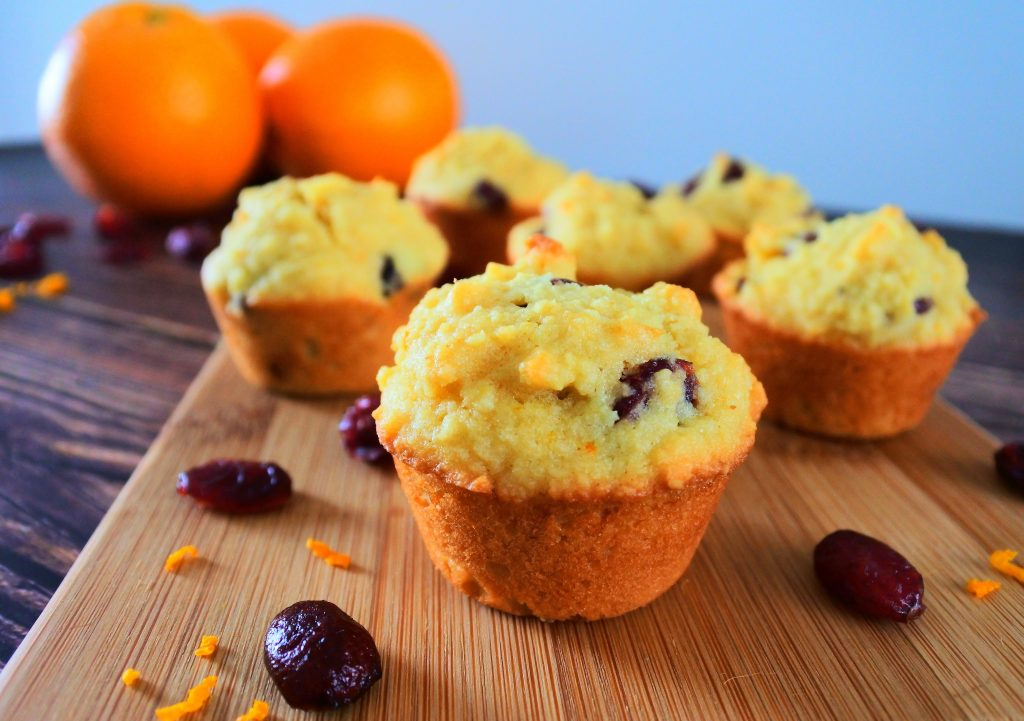 A close up image of some orange cranberry mini muffins on a wooden plank with dried cranberries and orange zest in the foreground and whole oranges in the background