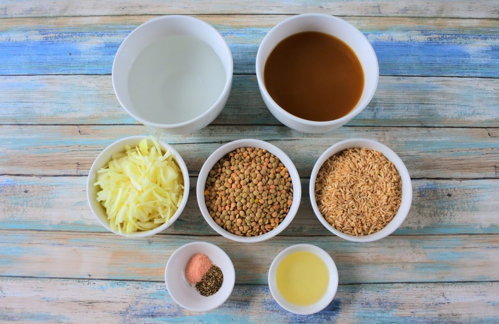 An overhead image of bowls of ingredients for mujadara including water, broth, sliced onions, dried lentils, brown rice, salt and pepper and extra light olive oil