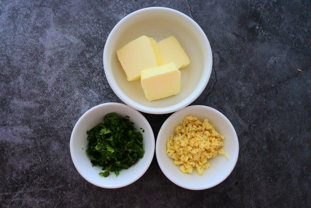 An overhead image of three bowls containing pats of butter, minced garlic and cilantro
