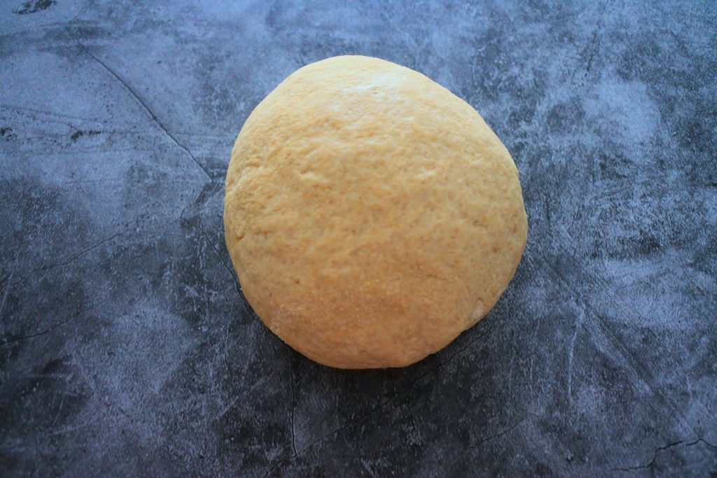 An overhead image of a kneaded ball of naan dough