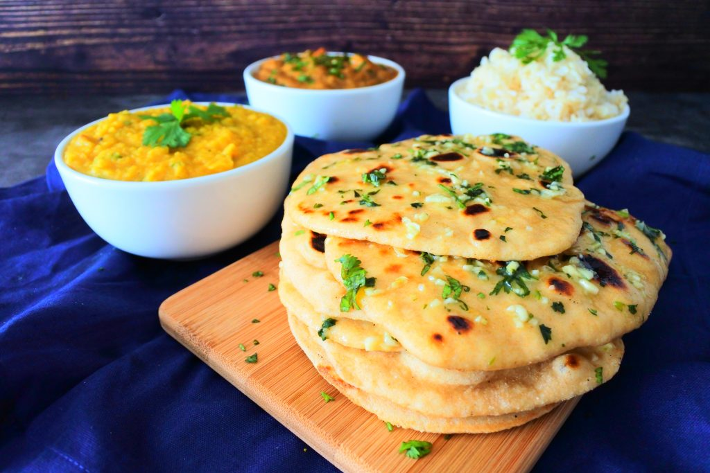 A close up image of a stack of garlic naan on a board with bowls of curry, dhal and rice in the background