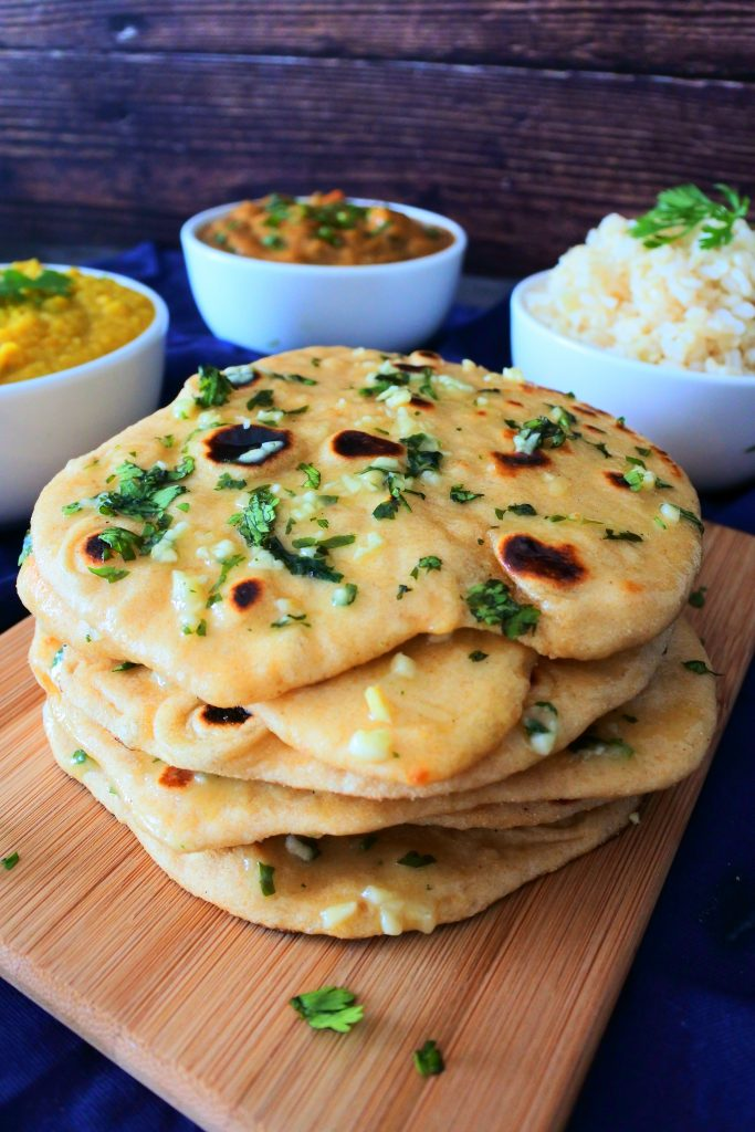 A close up vertical image of a stack of garlic naan on a board with bowls of curry, dhal and rice in the background