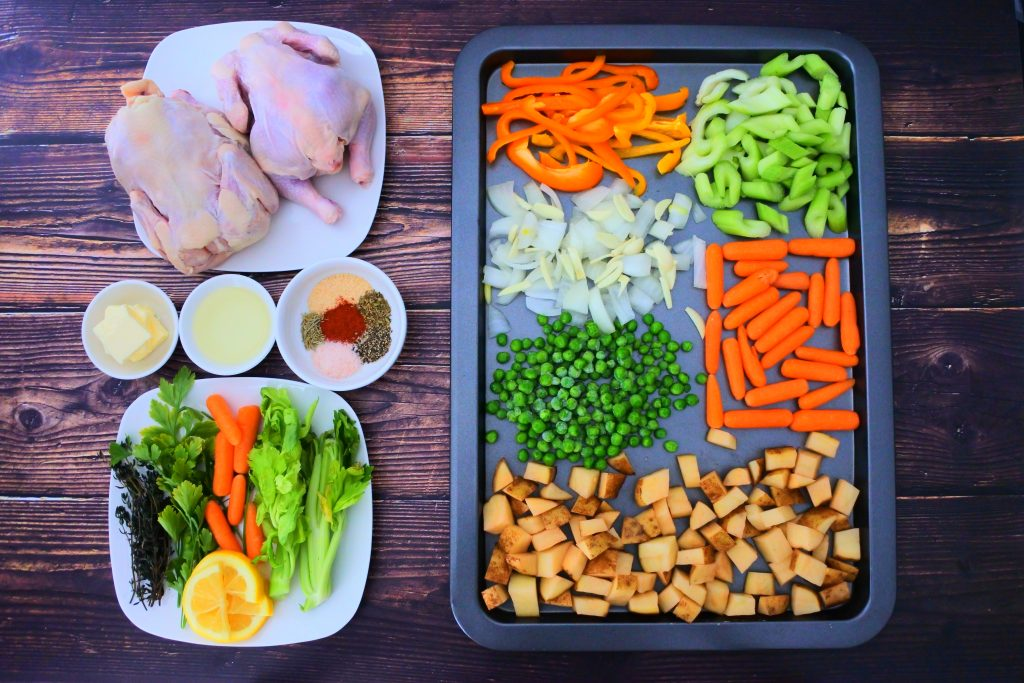 An overhead image of a tray of assorted vegetables along with a plate of two washed and dried cornish hens, a small dish of oil, butter, spices, and a plate of herbs and vegetables for stuffing the hens