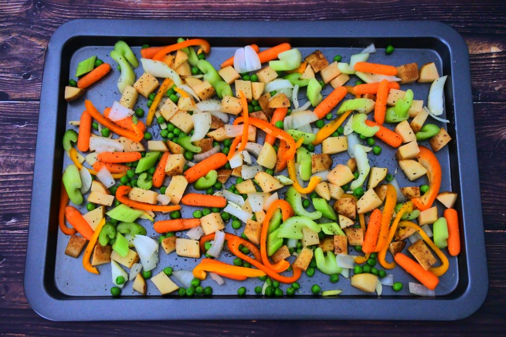 An overhead image of a tray of assorted sliced and seasoned vegetables
