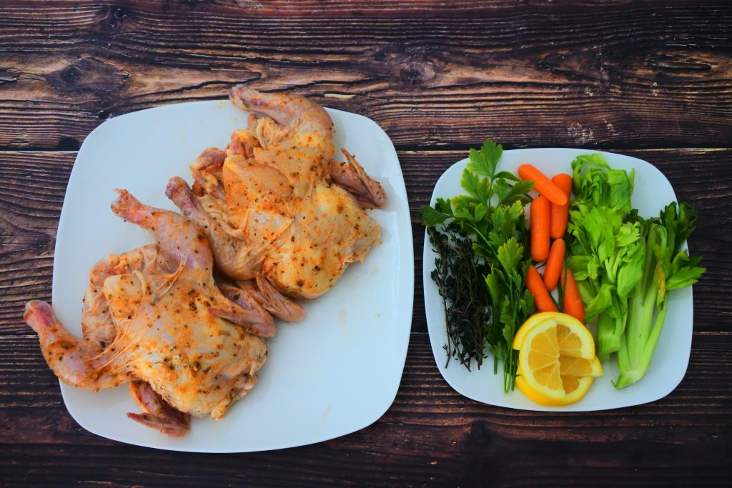 An overhead image of two cornish game hens with a rub next to a plate of herbs and vegetables for stuffing