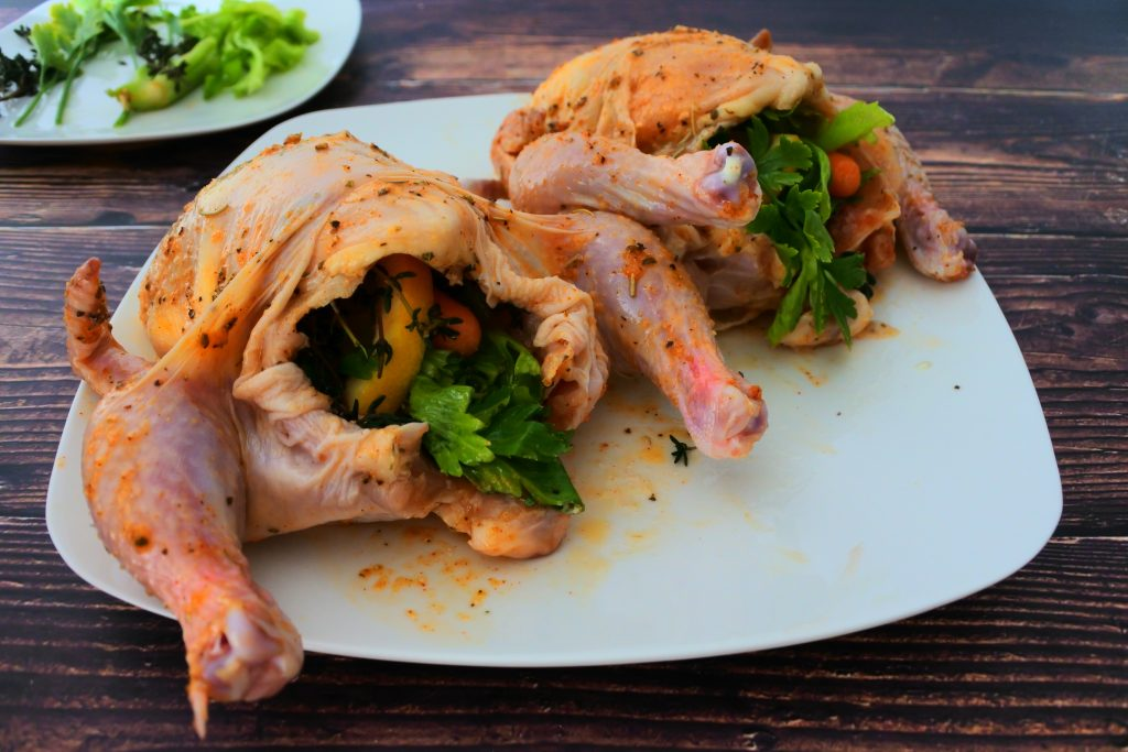 A close up image of two stuffed Cornish game hens on a plate
