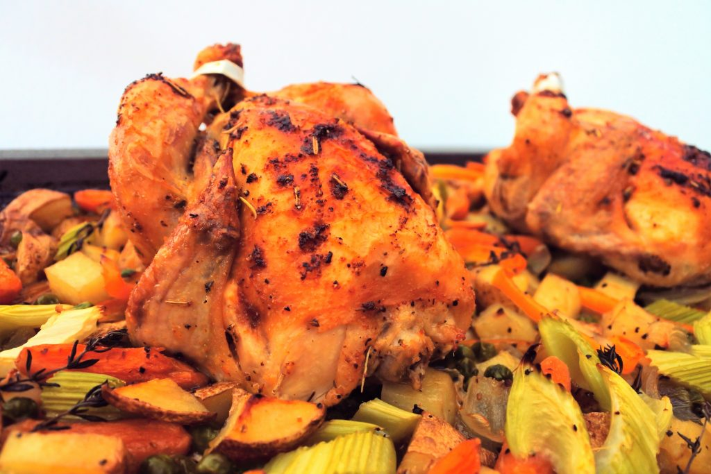 a close up image of baked cornish game hens on a bed of vegetables