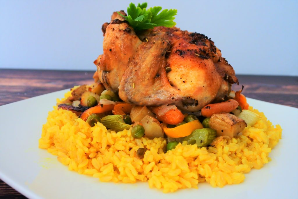 A close up image of a cornish game hen on a bed of vegetables and saffron rice