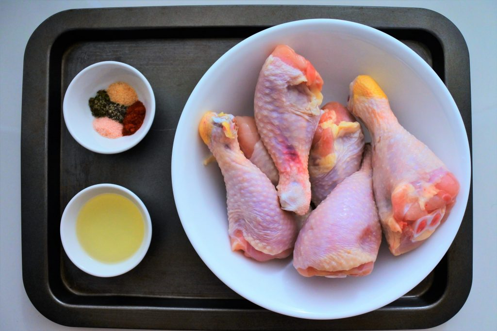 An overhead image of ingredients for pan fried chicken drumsticks including raw chicken drumsticks, oil and spices.