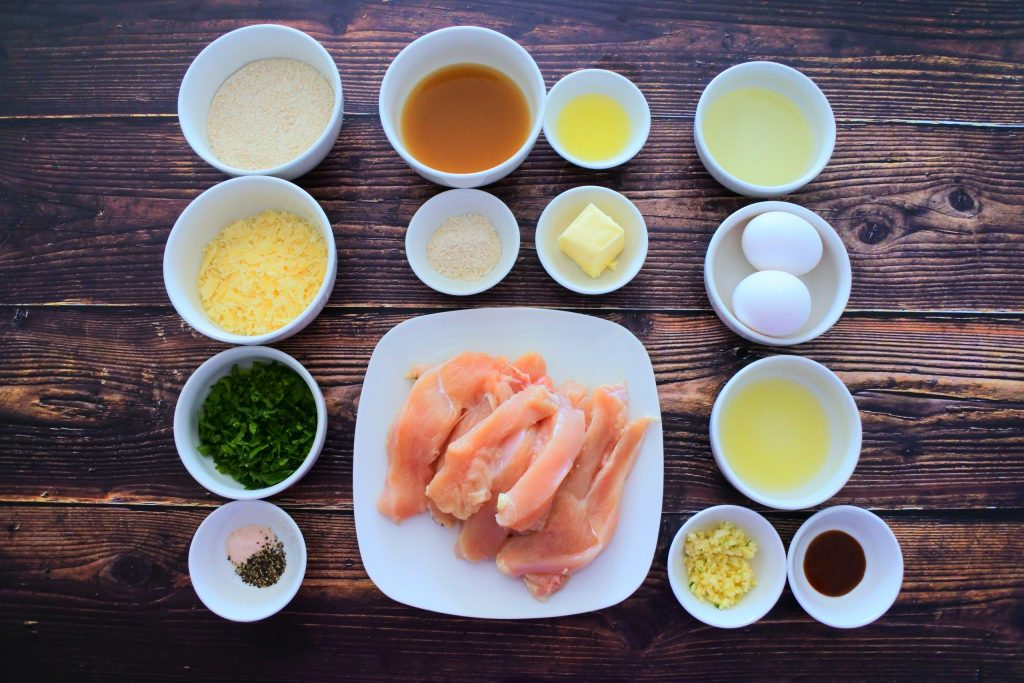 An overhead image of ingredients for herb crusted parmesan chicken including whole wheat flour, shredded paremensan cheese, herbs, salt, pepper, garlic, hot sauce, lemon juice, eggs, oil, and chicken breast cut into strips. And for a simple sauce, chicken bone broth, lemon juice, whole wheat flour and butter.