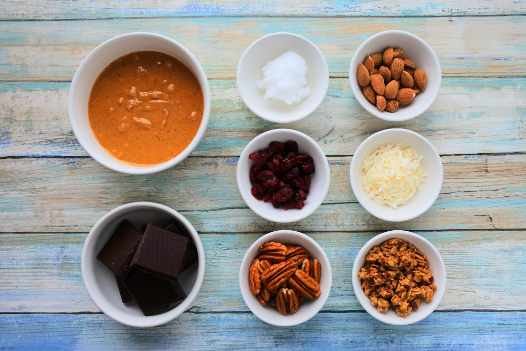 An overhead image of dishes of peanut butter, coconut oil, dark chocolate, almonds, dried cranberries, shredded coconut, pecans, and granola
