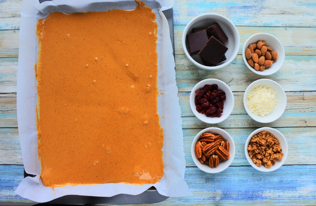 An overhead image of a tray of peanut butter with dishes of dark chocolate, almonds, dried cranberries, shredded coconut, pecans, and granola