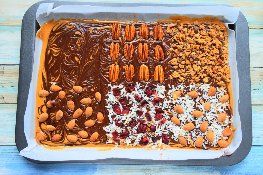 An overhead image of a tray of peanut butter and chocolate bark topped with various toppings included pecans, granola, almonds, shredded coconut and dried cranberries, and shredded coconut and almonds