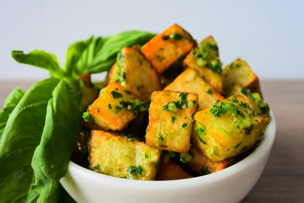 A head on close up image of a bowl of fried potato cubes tossed in pesto sauce