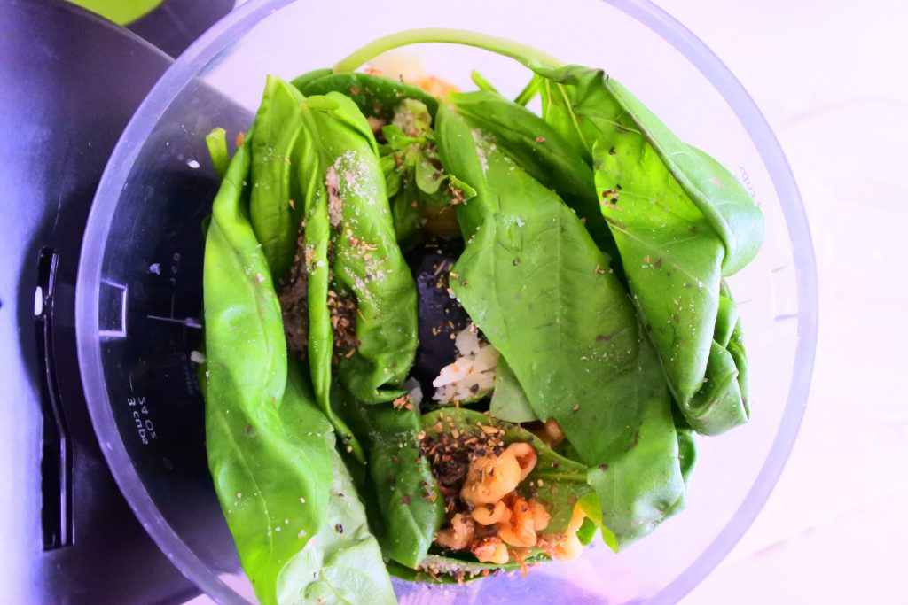 An overhead image of ingredients for a pesto in a food processor