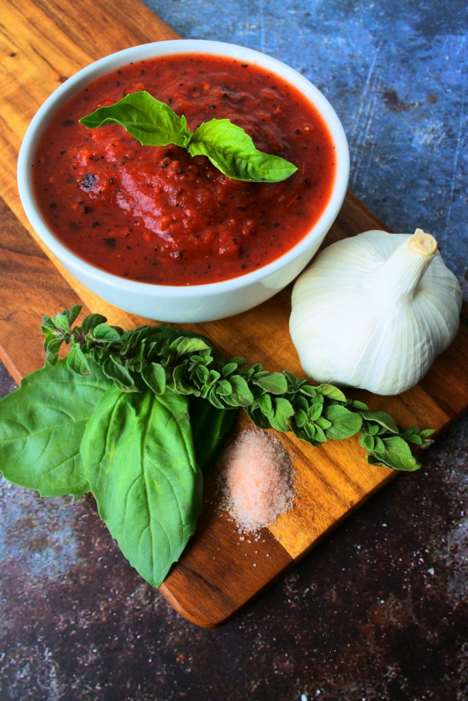 An overhead angled image of a bowl of tomato sauce with a sprig of basil in it on a wooden board with fresh herbs and salt