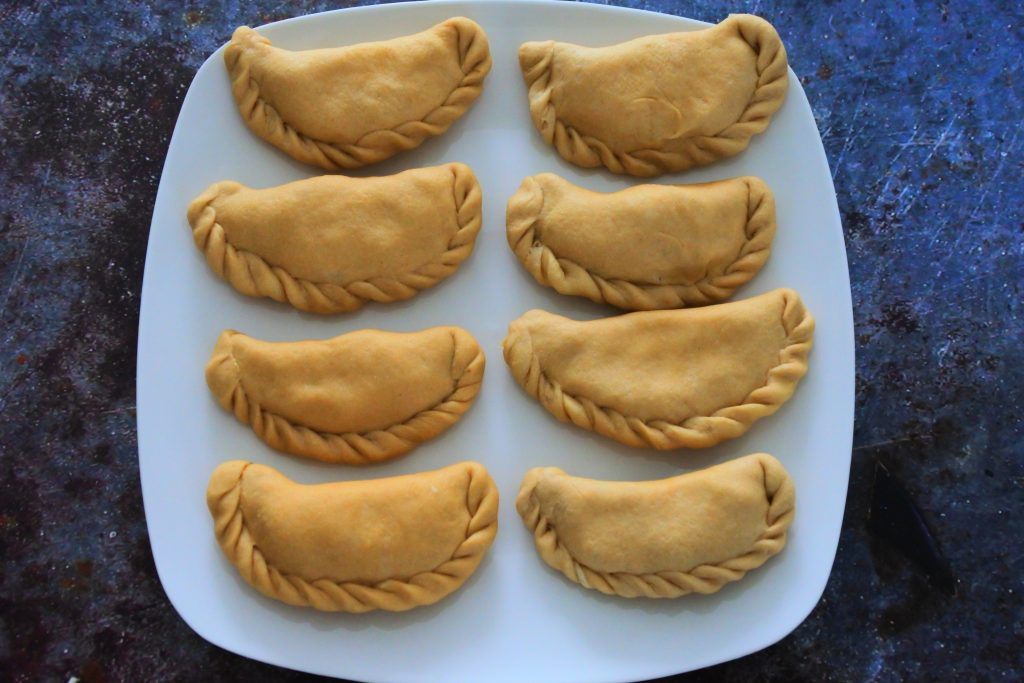 An overhead image of a plate of uncooked potato samosas aka aloo pies