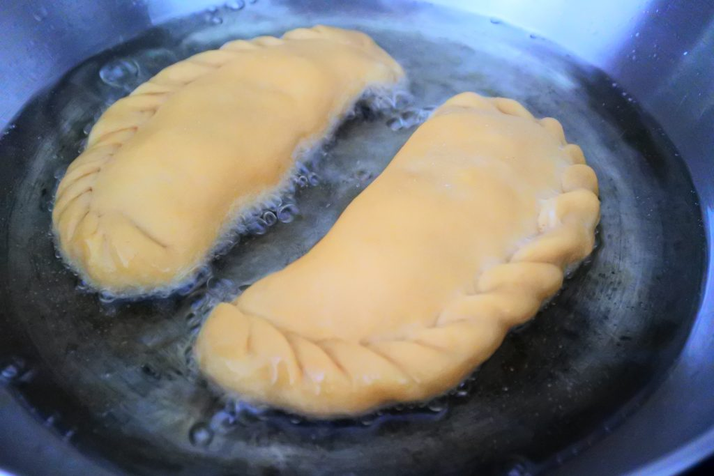 A close up image of potato samosas/aloo pies being added to a pan of shallow hot oil