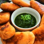 A close up image of a plate of potato samosas/aloo pies with a small bowl of cilantro dipping sauce in the middle and an adornment of fresh cilantro, lemon, garlic and potatoes in the background