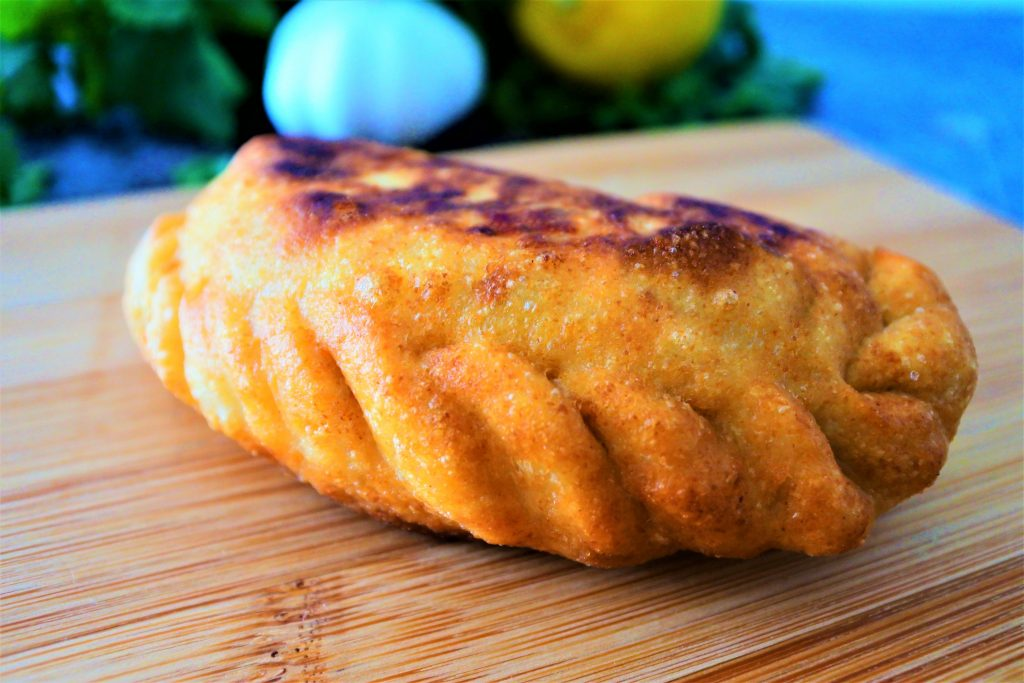 A close up image of a golden fried potato samosa/ aloo pie on a wooden plank