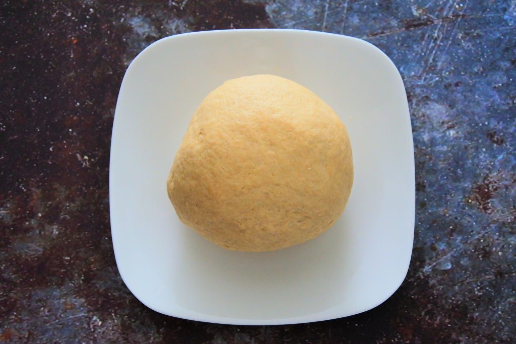 An overhead image of a plate with a large dough ball