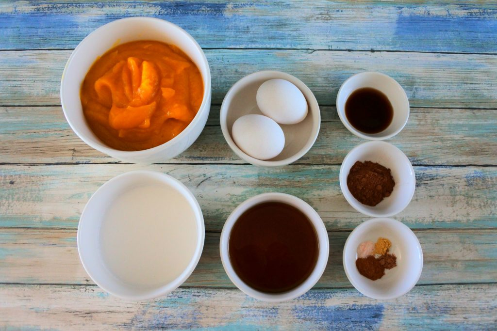 An overhead image of bowls of ingredients for pumpkin pie filling including pumpkin puree, coconut milk, whole eggs, maple syrup, vanilla extract, pumpkin spice, salt, cinnamon, ginger, and nutmeg