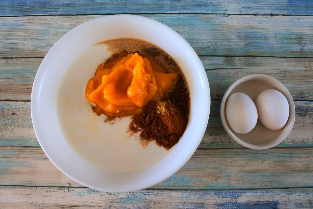 An overhead image of a large bowl with pumpkin puree, coconut milk, maple syrup and spices next to a smaller bowl containing two whole eggs