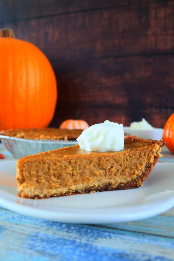 A vertical close up image of a slice of homemade pumpkin pie topped with coconut whipped cream on a white place with a large pumpkin in the background