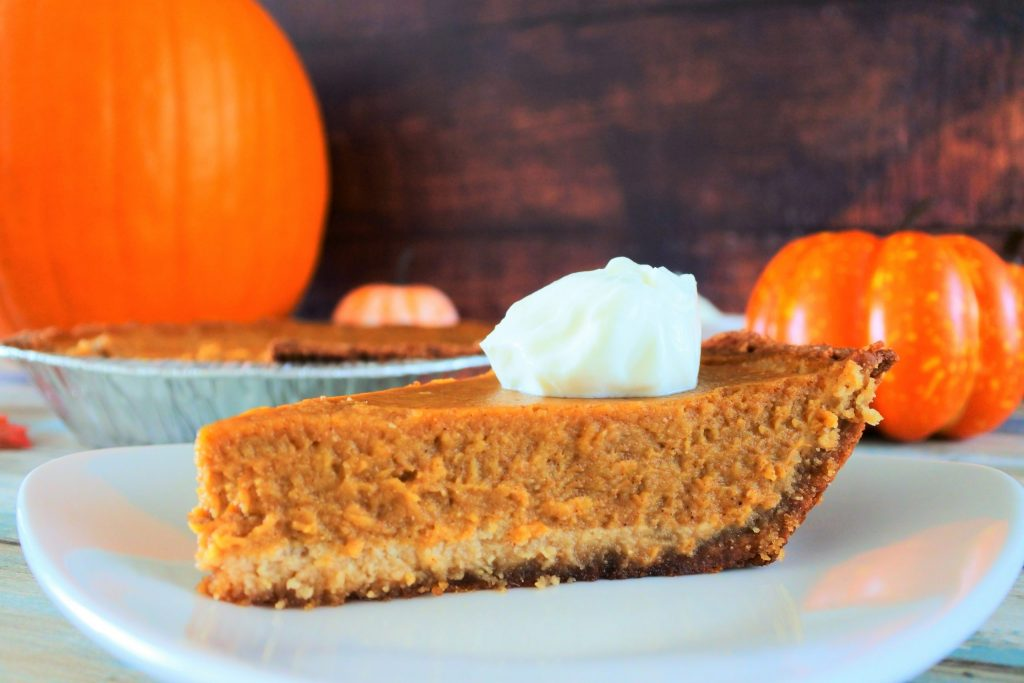 A close up image of a slice of pumpkin pie on a plate topped with a dollop of coconut whipped cream on a plate with a pie tin and pumpkins in the background