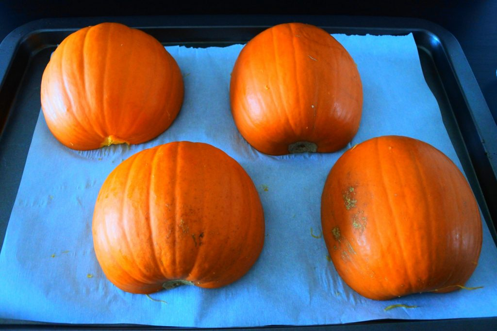 An angled image of pumpkin halves on a baking tray lined with parchment paper