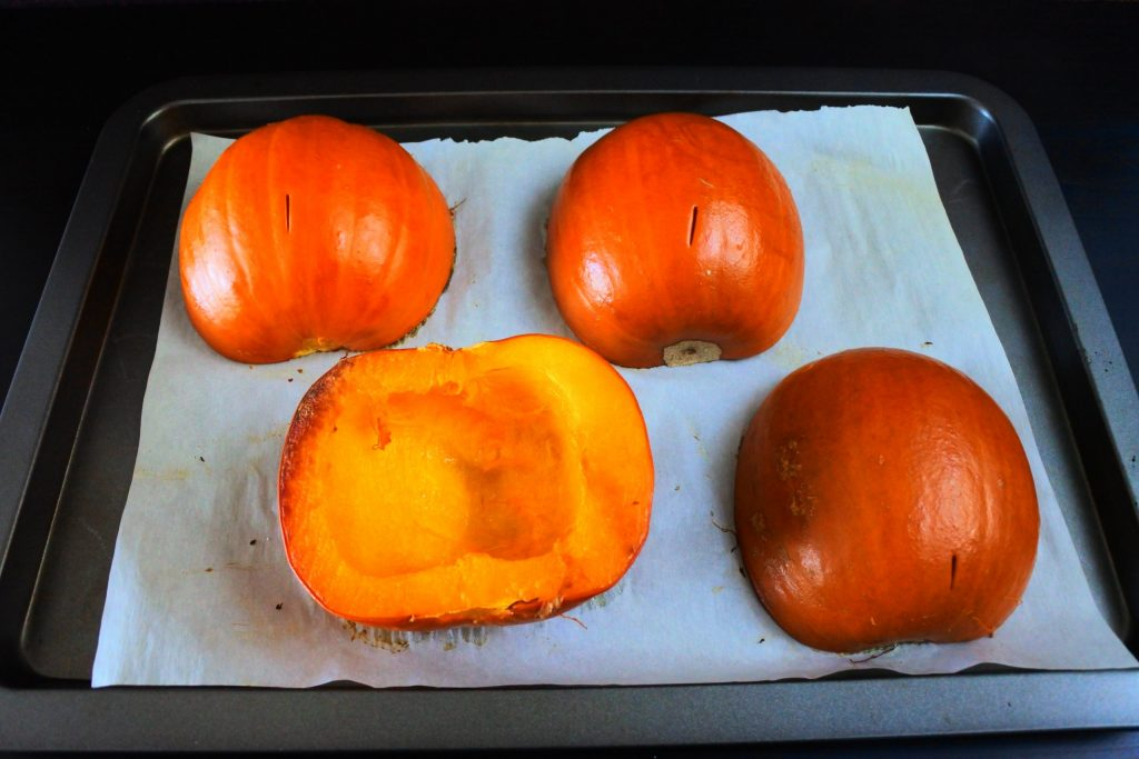 An angled image of oven roasted pumpkin halves on a baking tray lined with parchment paper