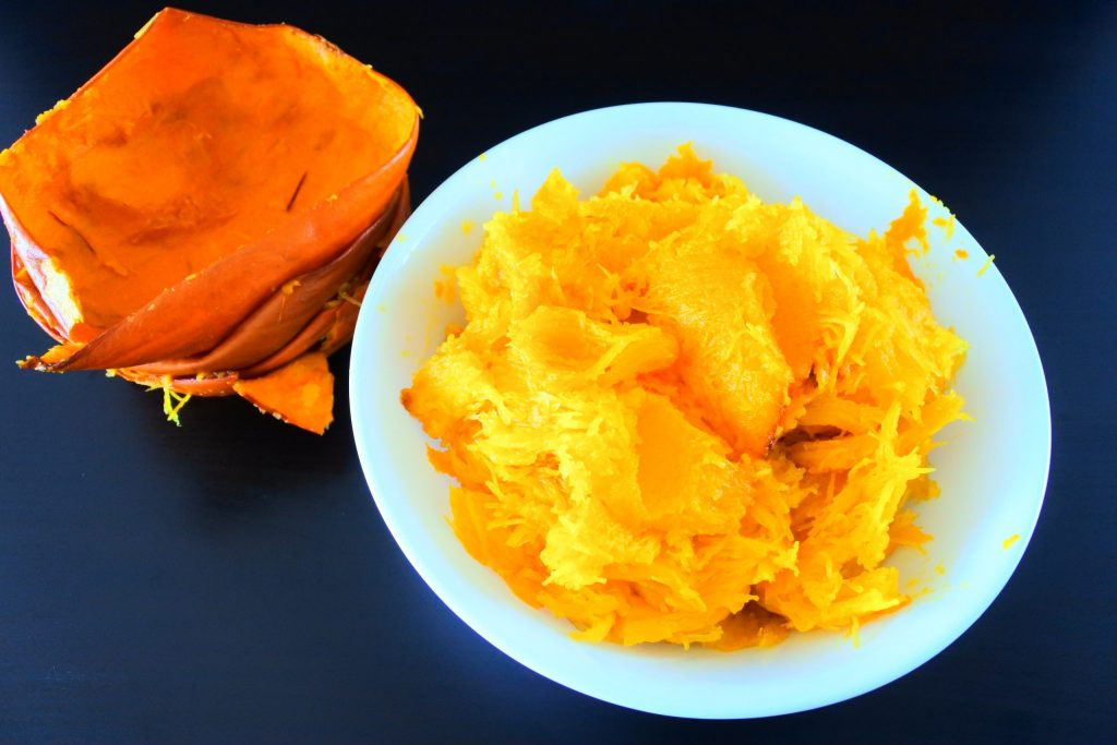 An overhead image of a bowl of oven roasted pumpkin flesh with scraped out pumpkin skins
