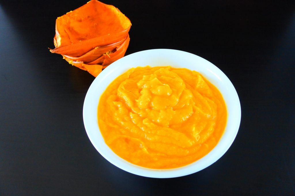 An overhead image of a bowl of pumpkin puree with scraped out pumpkin skins